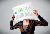 Woman holding a paper with charts and cityscape in front of her — Stock Photo