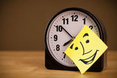 Post-it note with smiley face sticked on a clock — Photo
