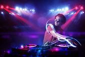 Diskžokej hraje hudbu s účinky světla na scéně — Stock fotografie