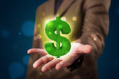 Young businessman presenting green glowing dollar sign — Stock Photo