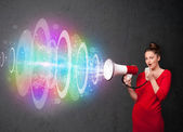 Young girl yells into a loudspeaker and colorful energy beam com — Stock Photo