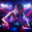 Stock Photo: Disc jockey girl playing music with light beam effects on stage