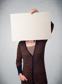 Woman holding in front of her head a paper with copy space — Stock Photo
