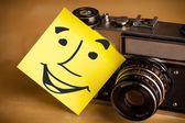 Post-it note with smiley face sticked on a photo camera — Stock Photo