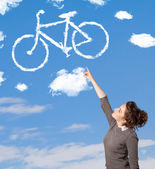 Young girl looking at bicycle clouds on blue sky — Stock Photo