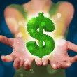 Young woman presenting green glowing dollar sign — Stock Photo