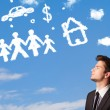 Businessman daydreaming with family and household clouds — Stock Photo #34420521