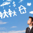 Stock Photo: Businessman daydreaming with family and household clouds