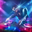 Stock Photo: Energetic Dj mixing music with powerful light effects