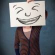 Woman with drawed smiley face on a paper in front of her head — Stock Photo #34425979