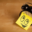 Post-it note with smiley face sticked on clock — Stock Photo #34853279