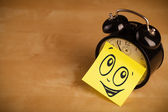 Post-it note with smiley face sticked on clock — Stock Photo