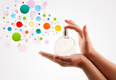 Woman hands spraying colorful bubbles from beautiful perfume bottle — Stock Photo