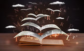 Pages and glowing letters flying out of a book — Stock Photo