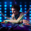 Young Dj mixing records with colorful lights — Stockfoto