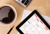 Tablet pc kalendarz wyświetlone na ekranie przy filiżance kawy na d — Zdjęcie stockowe