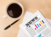 Tablet pc shows news on screen with a cup of coffee on a desk — Stockfoto