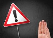 счастливый смайлик пальцы, глядя на треугольник предупреждающий знак с excla — Стоковое фото