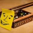 Post-it note with smiley face sticked on a box — Stock Photo