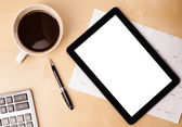Tablet pc with empty space and a cup of coffee on a desk — Stockfoto