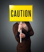 молодая женщина с табличкой осторожность — Стоковое фото