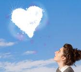 Ragazza carina guardando nuvola cuore bianco su blu cielo — Foto Stock