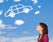 Young girl looking at car cloud on a blue sky — Stock Photo