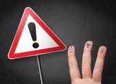 Doigts de smiley heureux regardant le panneau d'avertissement triangle avec excla — Photo