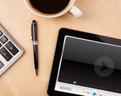Tablet pc showing media player on screen with a cup of coffee on — Stockfoto