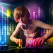 Dj girl playing songs in a disco with light show — Stock Photo