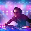 Disc jockey mixing music on turntables on stage with lights and — Stok fotoğraf