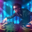 Dj mixing music in a club with blue and purple lights — Stock Photo