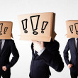 Men gesturing with exclamation marks on box on their head — Stock Photo
