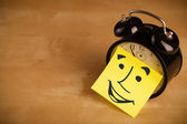 Post-it note with smiley face sticked on a clock — Stockfoto