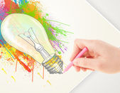 Hand drawing on paper a colorful splatter lightbulb — Stock Photo