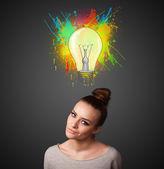 Mladá žena myslí s žárovka nad její hlavou — Stock fotografie