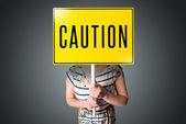 Mujer joven con un cartel de advertencia — Foto de Stock