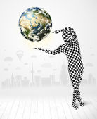Man in full body suit holding planet earth — Stock Photo