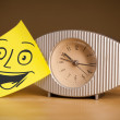 Post-it note with smiley face sticked on clock — Stock Photo #37087691