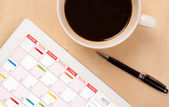 Tablet pc showing calendar on screen with a cup of coffee on a d — Stock Photo