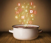 Glowing letters coming out from cooking pot — Stock Photo