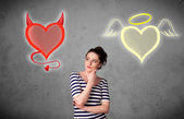 Woman standing between the angel and devil hearts — Stock Photo