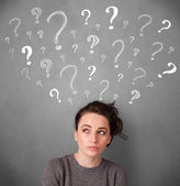 Young woman with question marks above her head — Stock Photo