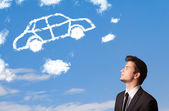 Handsome young man looking at car cloud on a blue sky — Stock Photo