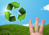Happy smiley fingers looking at green leaf recycle sign — Stock Photo
