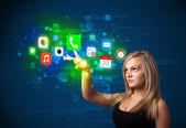 Young businesswoman pressing colorful mobile app icons with boke — Stok fotoğraf