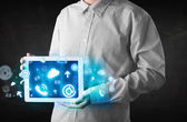Person holding a tablet with blue technology icons and symbols — Stock Photo