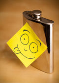 Post-it note with smiley face sticked on a hip flask — Stock Photo