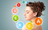 Pretty young girl with colorful vitamin icons and symbols — Stock Photo