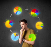 Young man thinking with pie charts circulation around his head — Stock Photo